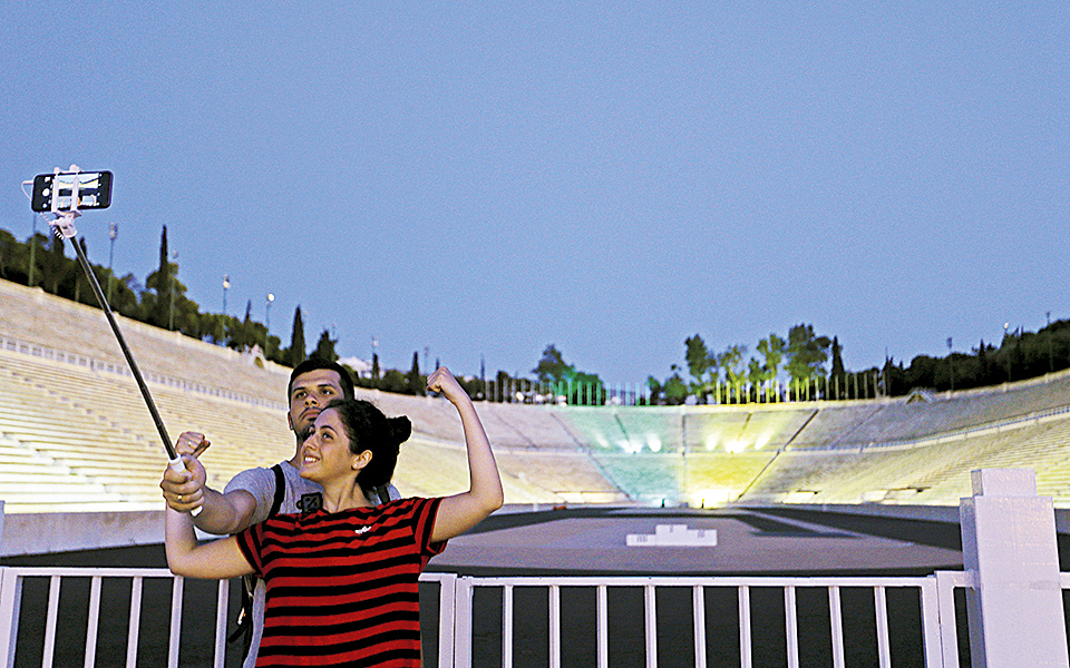 Tourists take photographs as a part of the refurbished ancient stadium in Athens, where the first modern Olympics were held in 1896, is floodlit in the Brazilian national colors on Thursday, Aug. 4, 2016. The event was held ahead of the Aug. 5-21 Games in Rio. The all-marble stadium was used in the 2004 Games in Athens for archery and the Marathon finish. (AP Photo/Thanassis Stavrakis)
