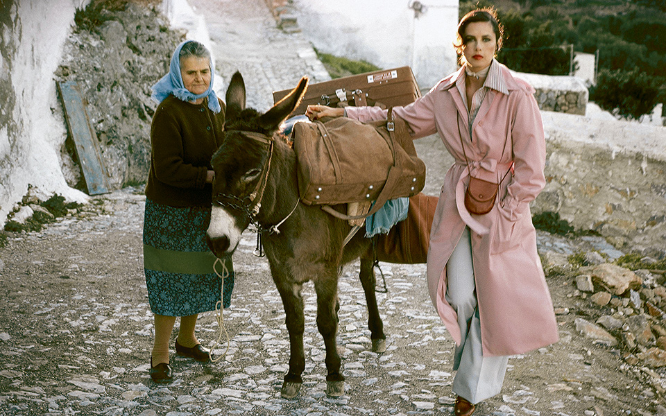 Model/actress Dayle Haddon with mule and Greek woman, wearing John Anthony's unlined raincoat over striped cotton shirt and garbardine trousers, also by John Anthony, brown Ultrasuede luggage by Halston for Hartmann, photographed in the village of Lindos, Greece. (Photo by Jacques Malignon/Condé Nast via Getty Images)